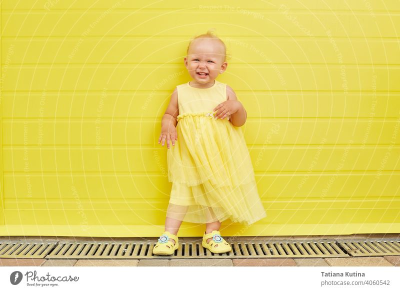 Adorable Little girl smiling on yellow background. kid fun childhood cute happy little todler cheerful smile portrait expression adorable young joy happiness