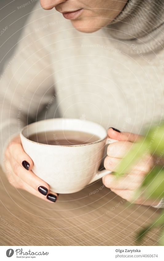 Woman holding a cup of tea. woman relax hand cosy drink close up caucasian break lifestyle girl morning comfort day adult sweater indoor soft focus table