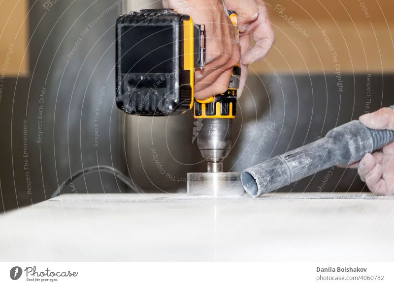 handyman cut round holes for electrical outlets in marble countertop for the kitchen using hand drill action appliance blade circle cleaner closeup construction