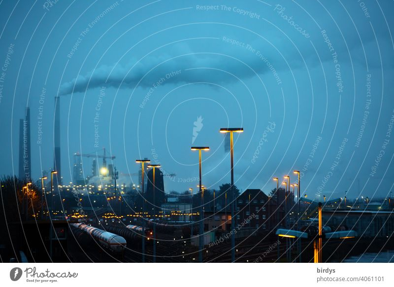 Industrial landscape at the blue hour. Smoking industrial chimneys , freight trains on tracks and many lights Industry Chemical Industry co2 Smoke exhaust gases