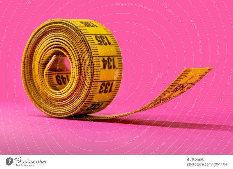 Macro shot of rolled up yellow tape measure on pink background Studio shot Studio lighting Pink Yellow Tape measure Coil meter tape Band Rollup Diet decrease