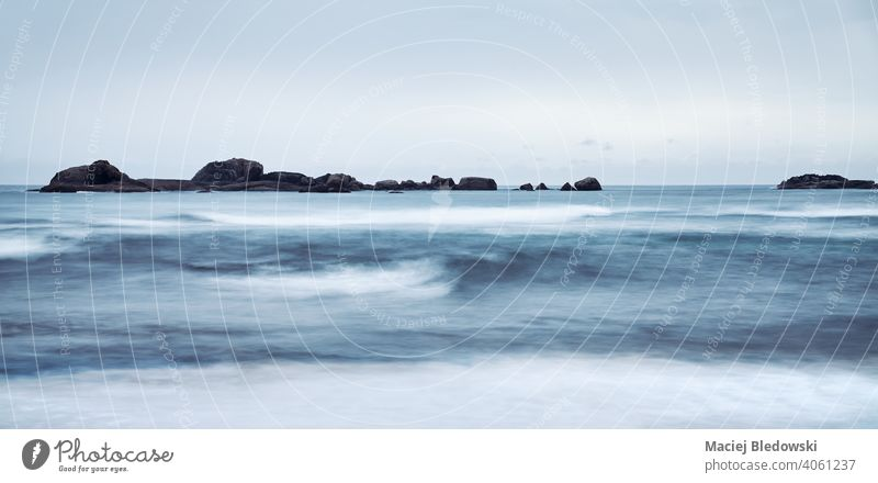 Long exposure picture of a seascape, focus on rocks, color toning applied. water wave dark ocean weather peaceful nostalgia sky long exposure toned horizon