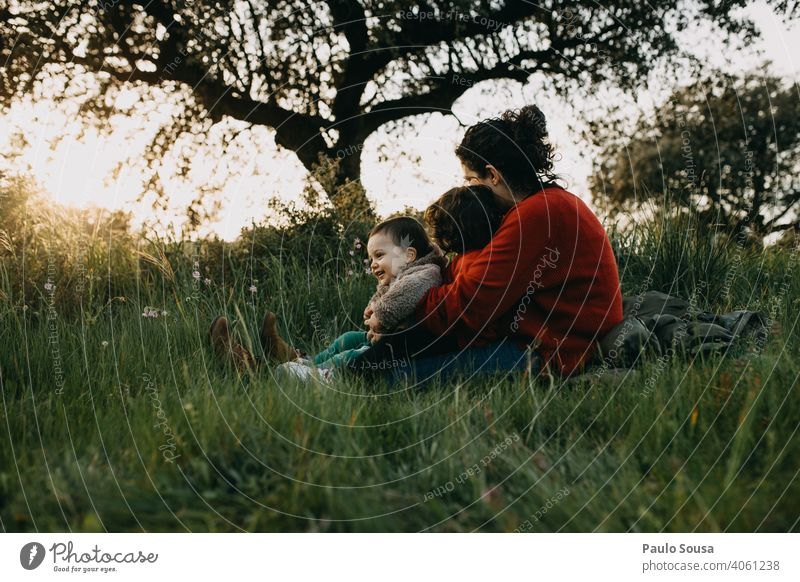 Mother hugging two children outdoors motherhood Mother's Day Motherly love Caucasian Family & Relations family Love Together togetherness care people Lifestyle