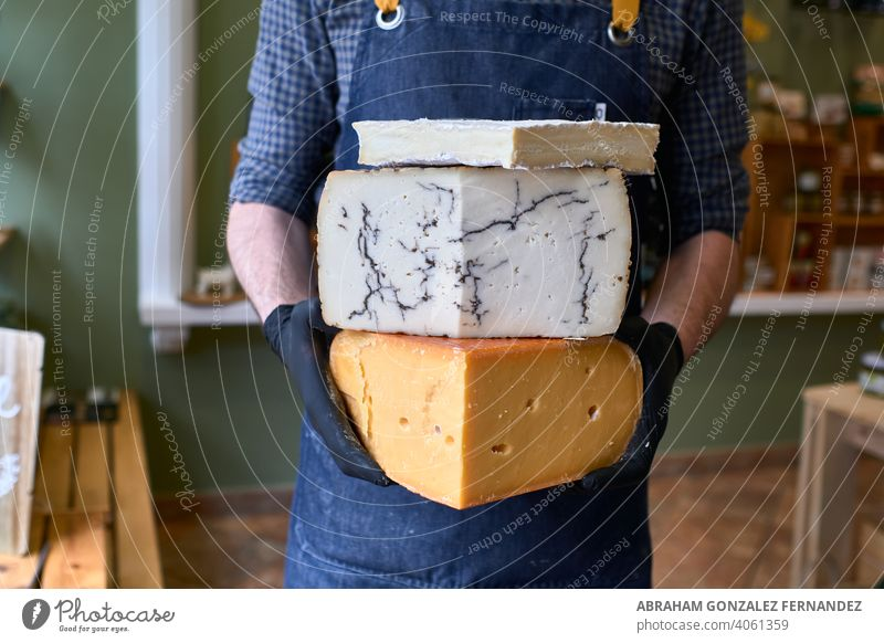 Portrait of a handsome cheese vendor in uniform holding three large cheeses in front of the store. delicatessen france artisan fromagerie shop person retail
