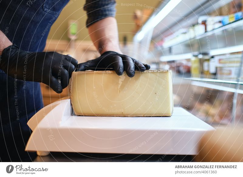 Male staff slicing a block of cheese in a local supermarket selective focus shot salesman holding shop store indoor businessman people sell male work food