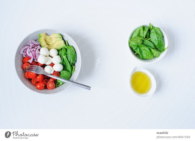 breakfast healthy diet bowl with cherry tomatoes, avocado, spinach leaves, Mozzarella and red onion with olive oil dressing vegetable salad food lime juice