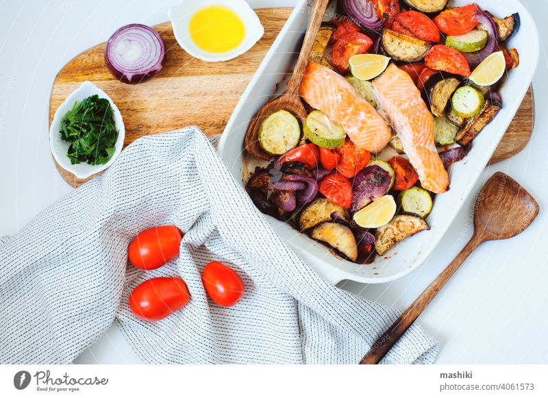oven roasted vegetable mix  - tomato, red onion, zucchini and eggplant with baked salmon. Healthy diet vegetarian dinner or lunch food healthy meal cooking