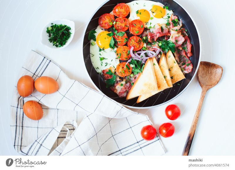 tasty comfort breakfast served in pan - fried eggs, cherry tomatoes, bacon, red onion and toasted bread. food meal meat cooked morning traditional dish