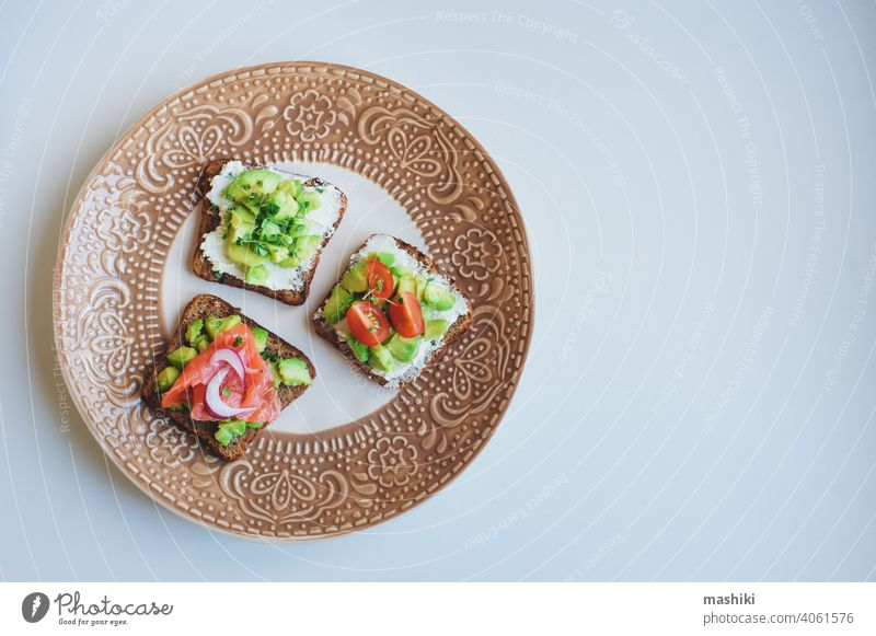 various toast served on plate, healthy breakfast with salmon, avocado, cream cheese, cucumber and red onion food sandwich bread snack meal fish lunch appetizer
