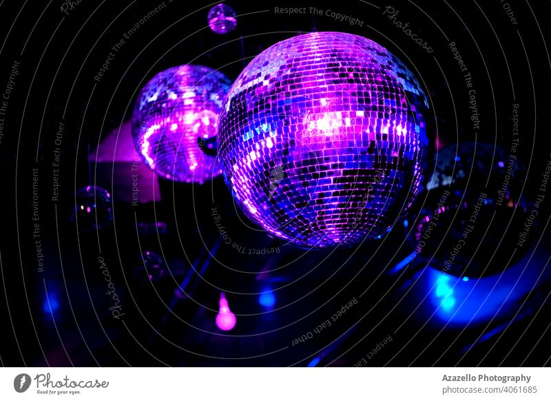 Disco ball in a night club in blue and purple lights. Mirror ball with reflections and beams. abstract backdrop background bright celebration colorful cool