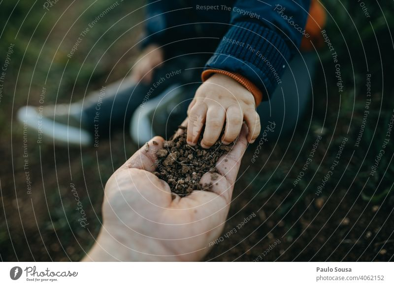 Child picking soil from father's hand childhood Education Close-up explore Authentic Colour photo Happiness Infancy Caucasian Joy Lifestyle Day Playing Happy