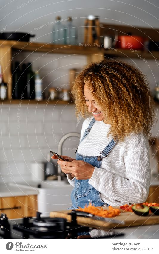 Woman texting with her smartphone. middle age couple love cooking home cozy caucasian relationship preparing female happy person stove kitchen woman alone