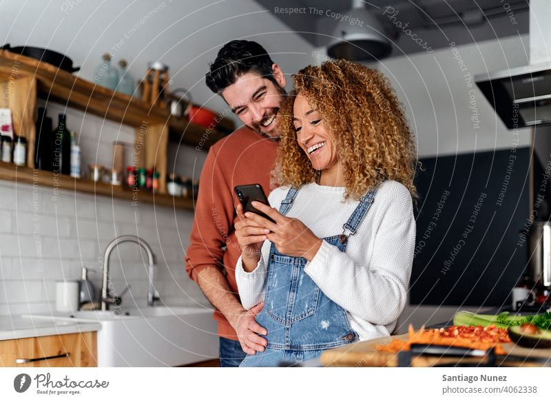 Couple looking at a smartphone in kitchen. middle age couple love cooking home cozy caucasian relationship preparing female happy person stove woman beautiful