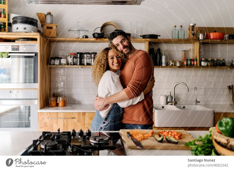 Couple hugging in the kitchen. middle age couple love cooking home cozy caucasian relationship preparing female happy person stove woman beautiful girl smiling