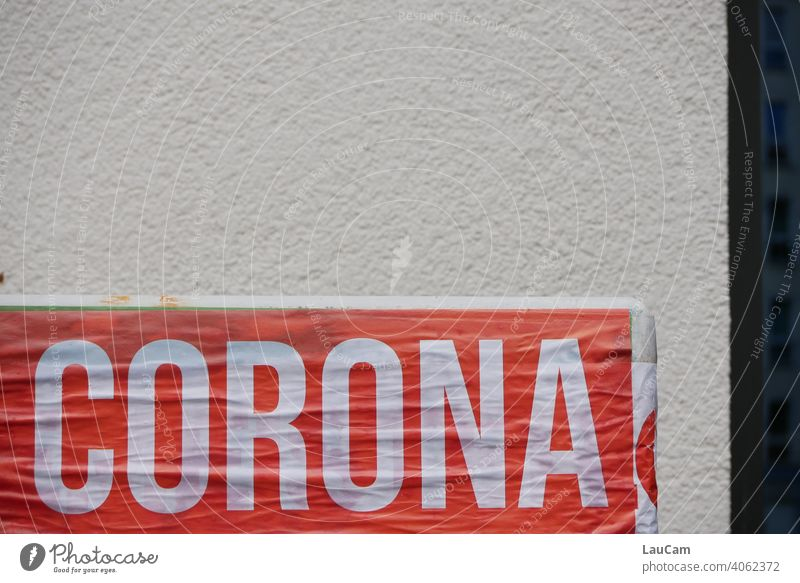 "White lettering ""Corona"" on red background in front of light house wall corona Virus coronavirus Corona Pandemic coronavirus SARS-CoV-2 corona crisis writing"