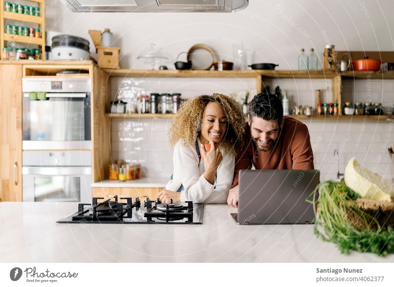 Couple looking at laptop in kitchen. middle age couple love cooking home cozy caucasian relationship preparing female happy person stove woman beautiful girl