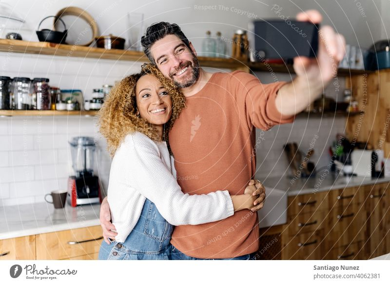 Couple taking a selfie standing in kitchen. middle age couple love cooking home cozy caucasian relationship preparing female happy person stove woman beautiful
