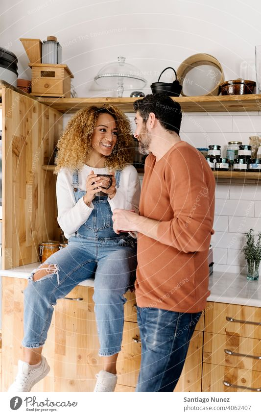 Couple laughing and standing in kitchen. middle age couple love cooking home cozy caucasian relationship preparing female happy person stove woman beautiful