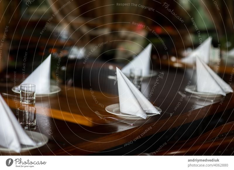 beautifully served table in a restaurant. selective focus. noise is present silverware set napkin luxury glass empty dish cutlery celebration service dinner