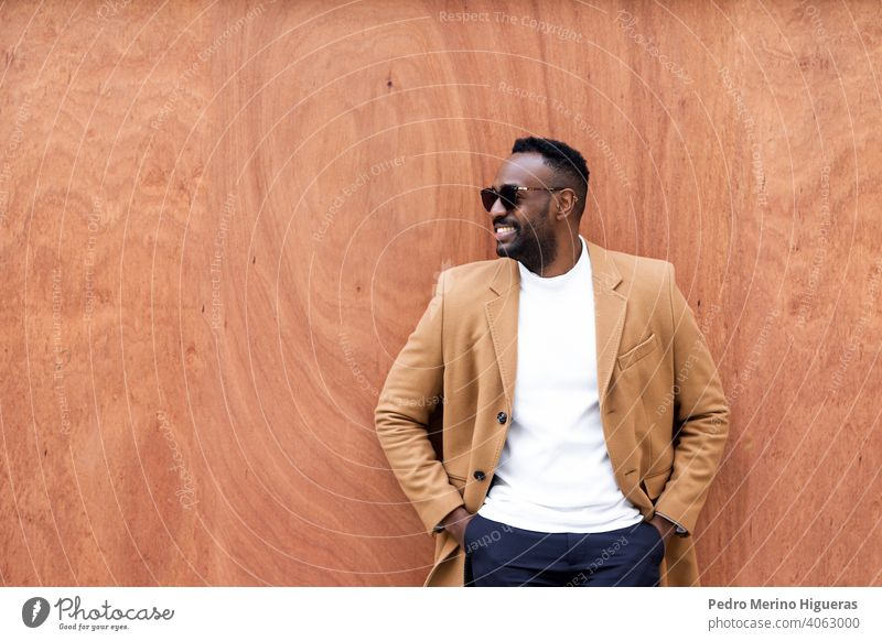 Handsome black man leaning against a wall looking aside smiling. african sunglasses leisure writing portrait city urban person lifestyle trendy standing male