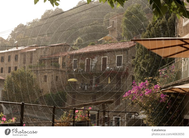 A refreshing rain shower descends on the village on the mountain daylight Day mountains Roof Architecture Village Building houses Tree Clouds Sky Sunshade