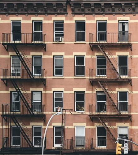 Old tenement house building with fire escapes, color toned picture, New York City, USA. city NYC retro symbol old residential home effect apartment Manhattan