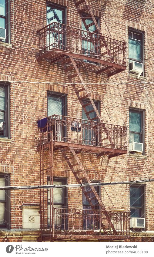 Old brick house building with iron fire escape, color toned picture, New York City, USA. city tenement NYC Manhattan townhouse retro old residential home effect