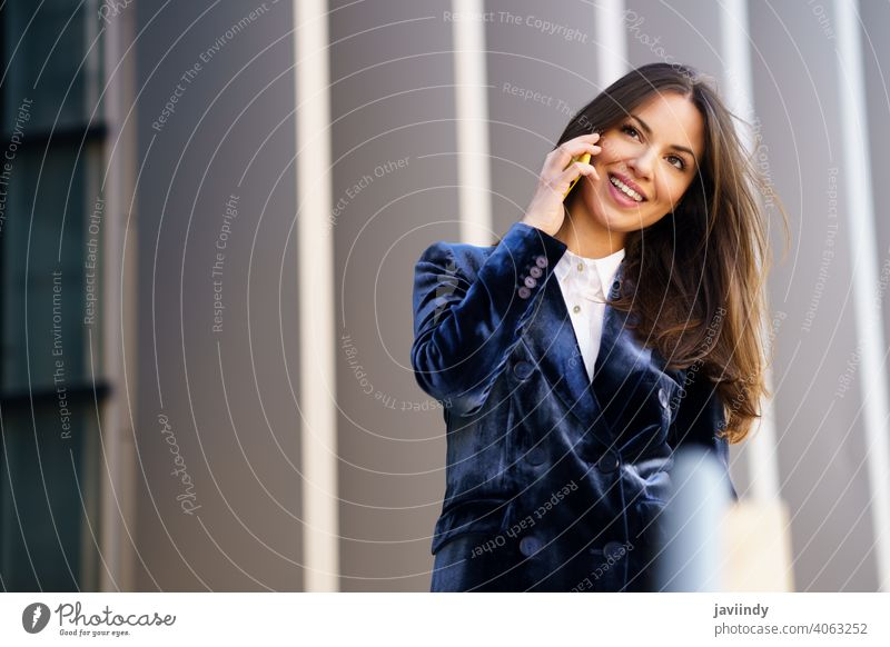 Business woman wearing blue suit using smartphone in an office building. businesswoman girl person device lifestyle female urban background lady elegant outside
