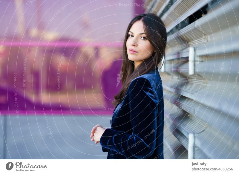Woman wearing blue suit posing near a modern building. woman girl pink person fashion model lifestyle female urban background lady one elegant blind outside