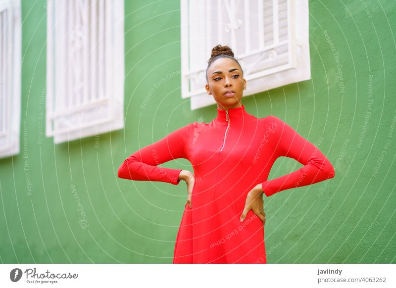 Young black woman in red dress in front of a green wall bow serious hairstyle model beauty fashion pretty portrait girl young female person lady summer white