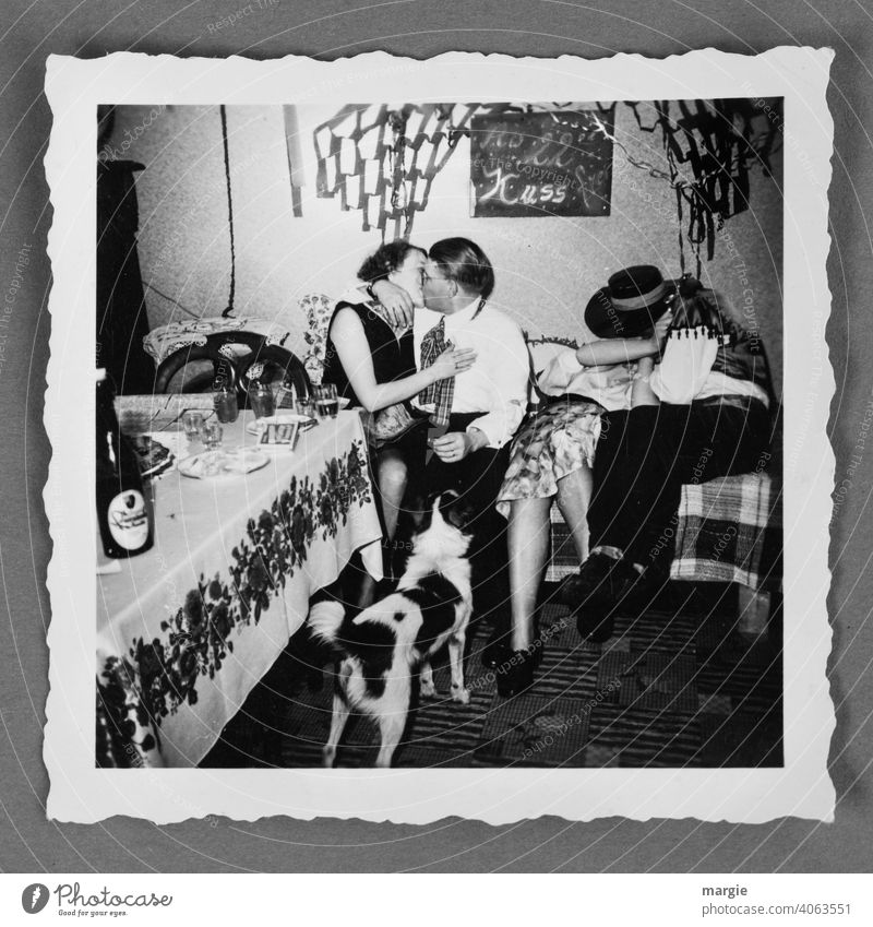 Text on a blackboard: From 10 pm kiss free! Two couples kissing in an analog photo. A dog is watching! Photography Analog Nostalgia family album Take a photo