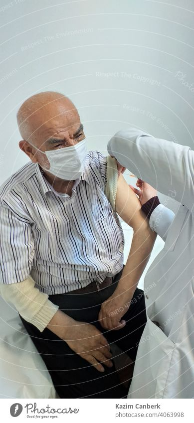 Old Turkish man getting Covid 19 vaccine to his arm by a nurse at a hospital covid 19 shot injection coronavirus pandemic epidemic old bearded turkish needle