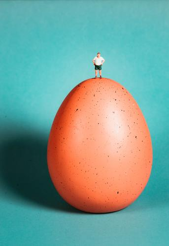 Man with green stands on an egg Miniature Minimalistic fake Artificial Artistic Easter egg hunt eggs Eggshell Studio lighting Religion and faith Jesus Christ