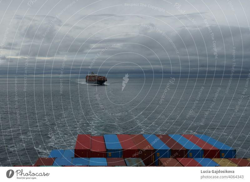 View on container vessel from other ship underway approaching the port of Vancouver, Canada, from Pacific ocean in the Salish Sea area. background bay blue boat