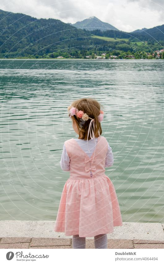A girl with a wreath of flowers stands by the lake and looks into the distance Colour photo Girl Human being Dress up Infancy Crown Happiness muck about Child