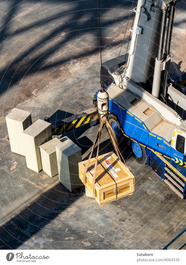 The crane lifting the radioactive instrument holder transportation wooden box work carry tall machinery industrial heavy equipment package radioactivity