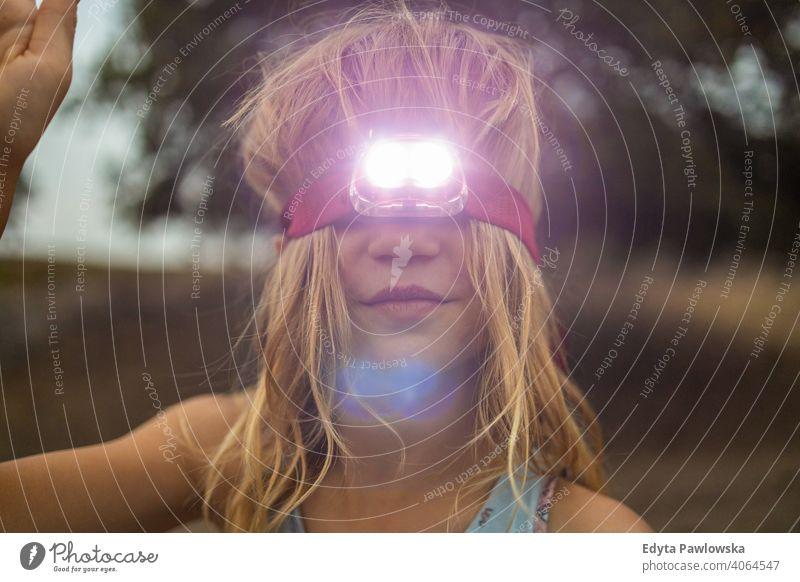 Girl with Head Torch Outdoors fun people summer camping retro vintage flashlight travel adventure outdoors childhood kid head torch headlamp evening dark adult