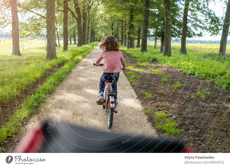 Little girl cycling in the countryside family safety people girls children kids biking bike cycle Europe Holland Netherlands Outdoor nature back rear view grass