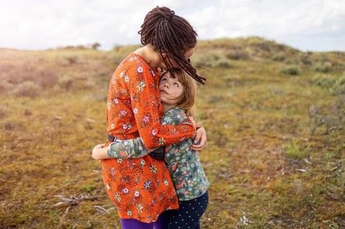 Mother and daughter embracing outdoors mother child family nature hipster dreadlocks love hugging adult beautiful beauty childhood culture dress female field