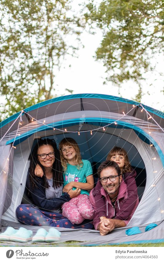 Happy family enjoying camping holiday hiking cycling vacation tent forest children kids happy smiling night evening trek trekking Wilderness wild nature green