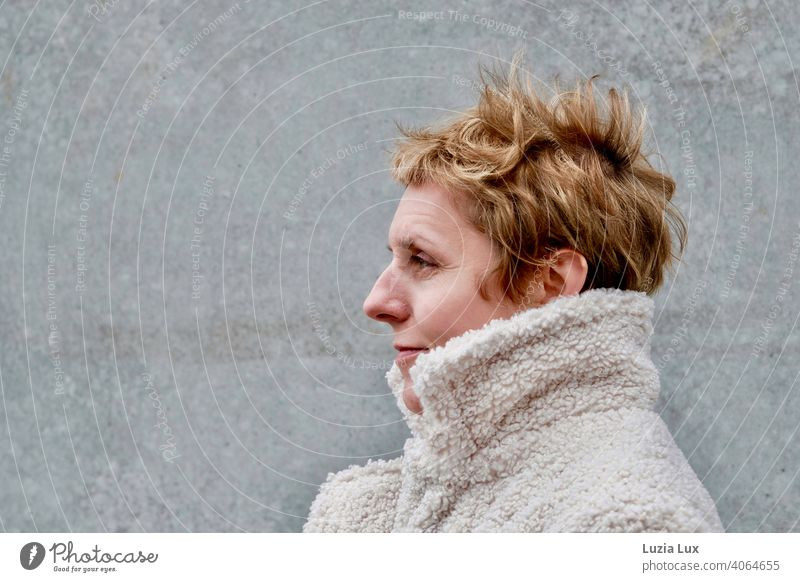 stormy: a pretty woman with very short blond hair in profile, snuggled up in a light coat. Woman portrait Profile Blonde Short-haired Adults Feminine Elegant