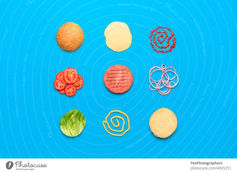 Burger ingredients top view isolated on blue background above view aligned arranged beef bread bun burger cheddar cheese cheeseburger colored concept cuisine