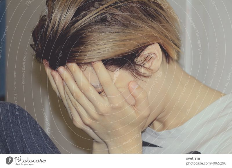 The girl covers her face with her hands. A young girl with blond hair sits in profile on the floor in a room against the backdrop of light-colored furniture and covers her face with her hands.