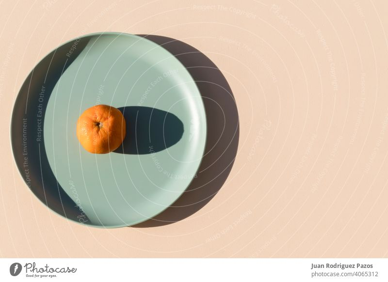 Minimalist image of a mandarin on a light green plate with a beige background. Top view. creative fruit minimal orange geometric shape food healthy color