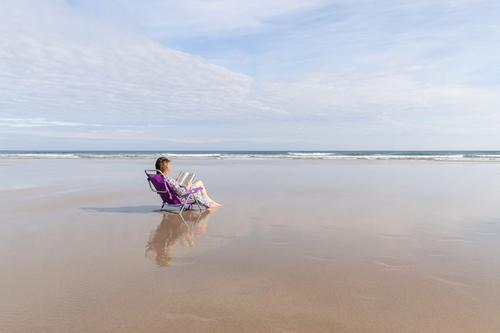 Woman reading a book sitting on a chair on a lonely beach sea outdoor social distance woman relax peaceful lifestyle vacation girl leisure female ocean shore