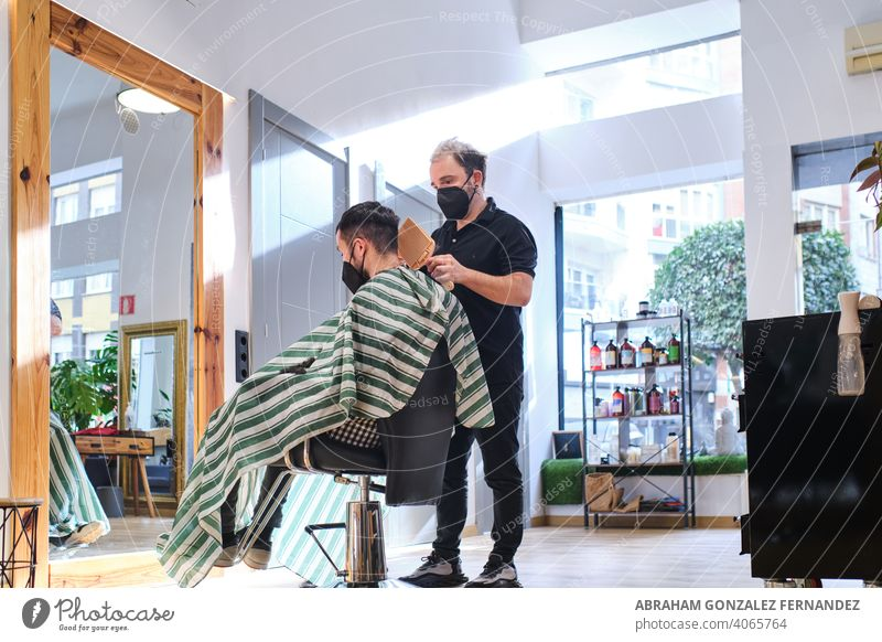 hairdresser cutting hair of male client. Hairstylist serving client at barber shop. barbershop face mask salon men customer virus business hairstylist lifestyle