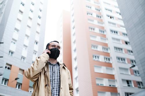 man wearing a protective face mask talking on a cell phone between tall buildings male mobile businessman virus epidemic protection midtown safety disease