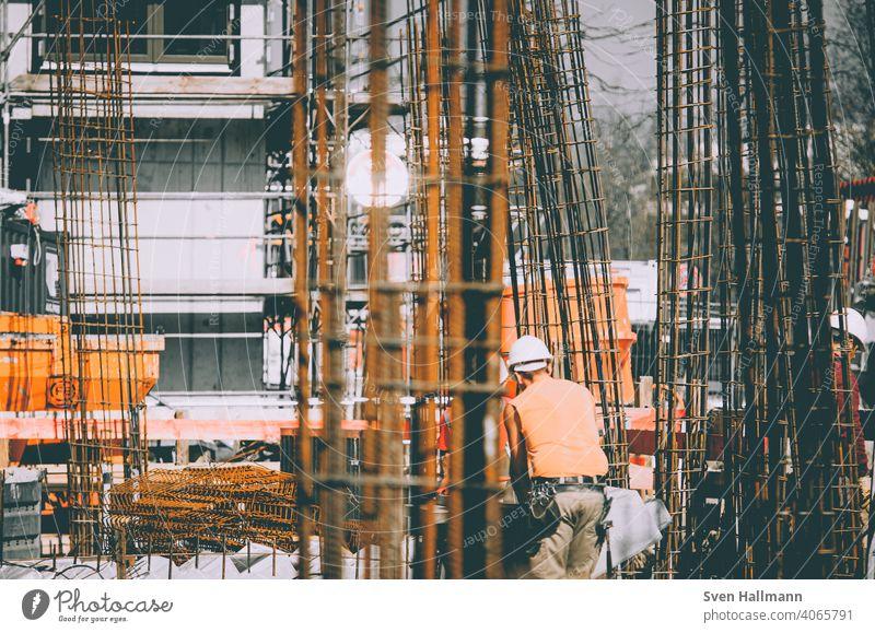 Construction worker next to steel girders Construction site Steel girder orange Tree Craftsperson Man Architecture Build Manmade structures Building Metal Crane