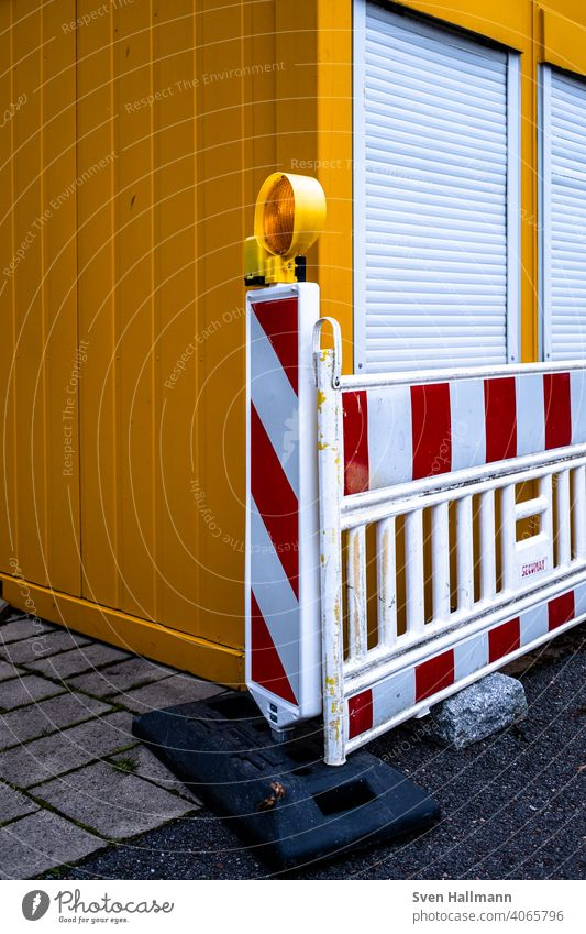 red-white barrier in front of container cordon Construction site Container shutters Striped Orange Red Protection Safety Exterior shot Bans barrier tape