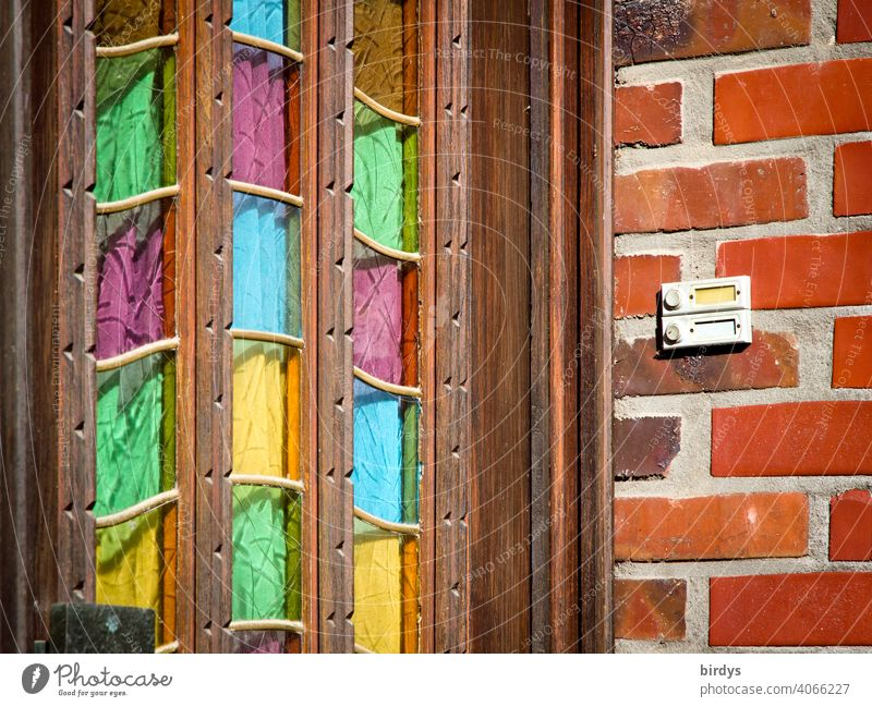 Old wooden house entrance door with coloured glass panes, brick wall with bell.entrance front door Entrance Wooden door Glass panes variegated Multicoloured